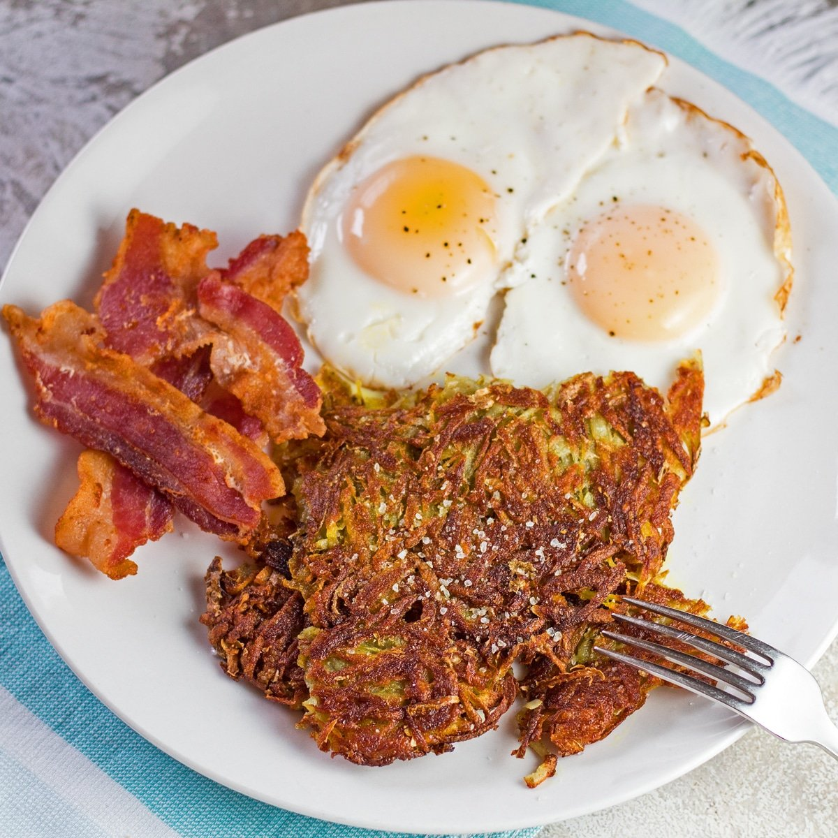 Large square angled overhead of the homemade hash browns plated in a 2 egg breakfast.