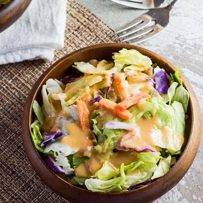 pequena imagem quadrada do molho de salada de gengibre benihana servido sobre a salada em uma tigela de bambu escuro com plano de fundo texturizado claro