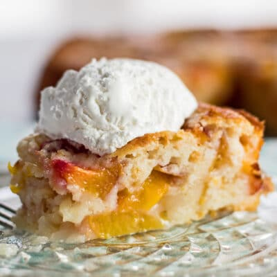 large square image closeu sideview of baked nectarine cobbler sliced and served with a scoop of whipped cream on a crystal plate with the cobbler in background