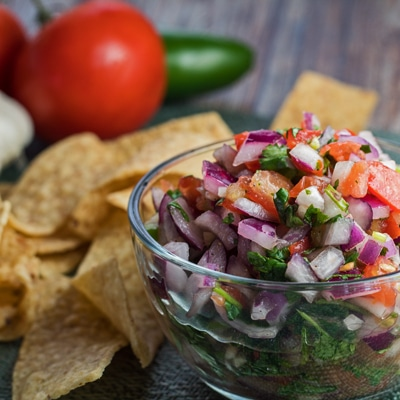 small square sideview image of pico de gallo with chips and fresh vegetables.