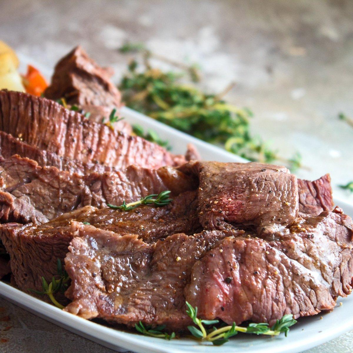 Önde dilimlenmiş et ve arkada istiflenmiş sebzelerle beyaz bir tabakta servis edilen güveç yankee rostosunun büyük kare görüntüsü.