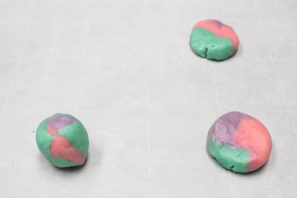 डबल चीनी कुकी आटा एक इंच की गेंद में लुढ़का हुआ है और बेकिंग के लिए नीचे गिरा दिया गया है
