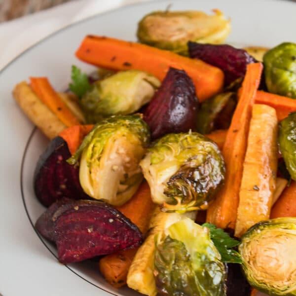ristet vegetabilsk medley af roer gulerødder pastinetter og rosenkål serveret i en hvid plade