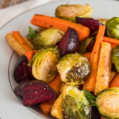 roasted vegetable medley of beets carrots parsnips and brussel sprouts served in a white plate