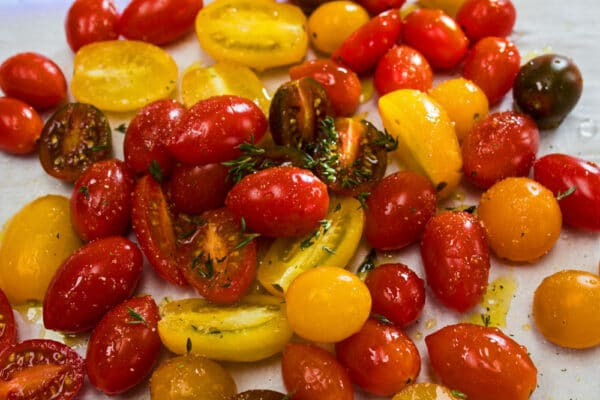 preparing cherry tomatoes on the baking sheet with olive oil and fresh thyme for seasoning