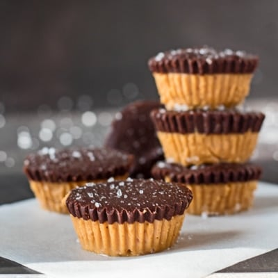 small square sideview image of dark chocolate almond butter cups with one at the front and several stacked behind with grey background