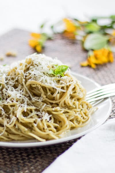 closeup vertical image of basil pesto pasta served on a white plate with brown background