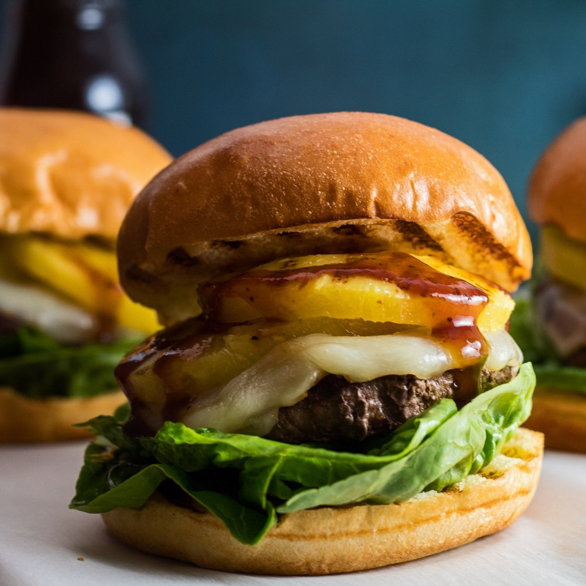 Large square image straight on closeup of the stacked Hawaiian Burger ingredients including ground beef patty, provolone cheese, grilled pineapple rings, lettuce, and teriyaki sauce on grilled brioche buns.