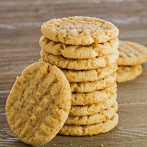 Imagen cuadrada grande de estas sabrosas galletas de mantequilla de almendras apiladas ocho galletas en alto con una inclinada contra el frente de la pila a la izquierda con fondo de madera marrón medio