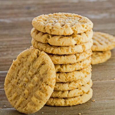 large square image of these tasty almond butter cookies stacked eight cookies high with one tilted against the front of the stack on the left with medium brown wooden background