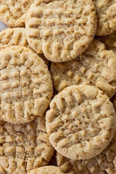 Imagen vertical de altura foto en primer plano de las galletas de mantequilla de almendras fáciles apiladas una encima de la otra