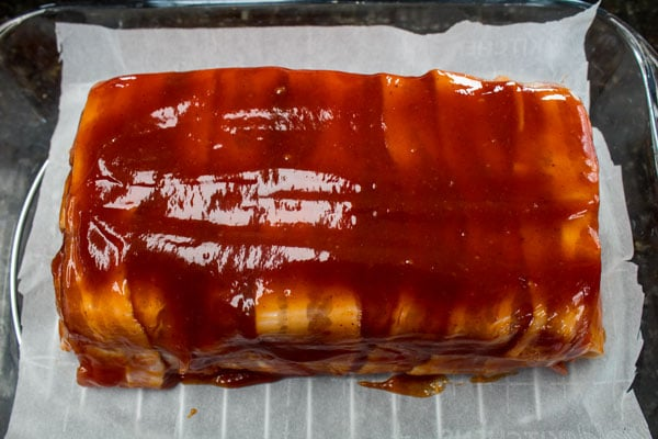 bacon wrapped meatloaf formed and topped with ketchup glaze and ready to be oven baked