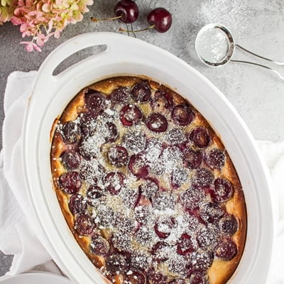 small square overhead image of the baked bing cherry clafoutis in the white oval baking dish with cherries scattered around on a light grey background