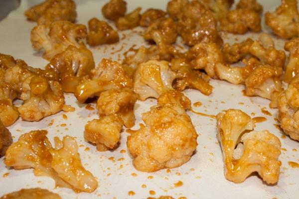 Rød Miso Sauce belagt blomkål arrangeret i et enkelt lag på pergamentpapir foret bageplade på Delectable, www.delectablecookingandbaking.com