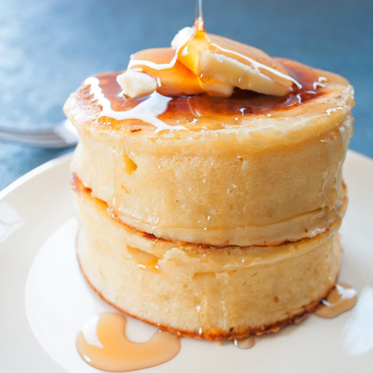 Stacked Japanese fluffy pancakes with butter and syrup.