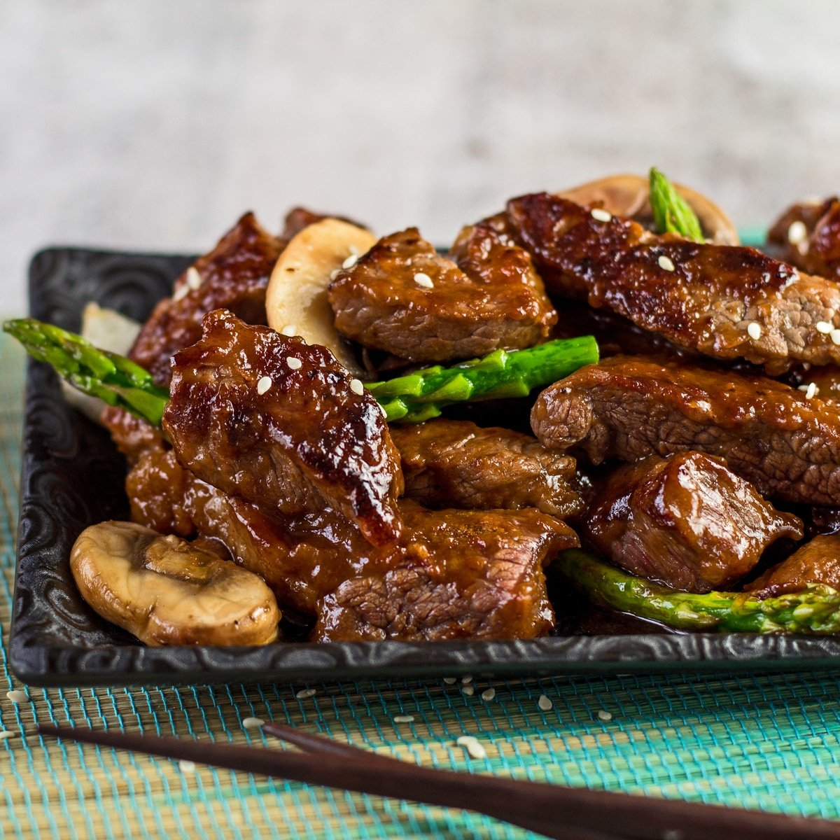Large square angled view of the left half of the served plate of panda express shanghai angus steak after being wok fried with onion mushroom and asparagus then tossed in the shanghai sauce.