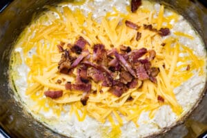 slow cooker crack chicken after cooking and shredding with cheese and bacon added.