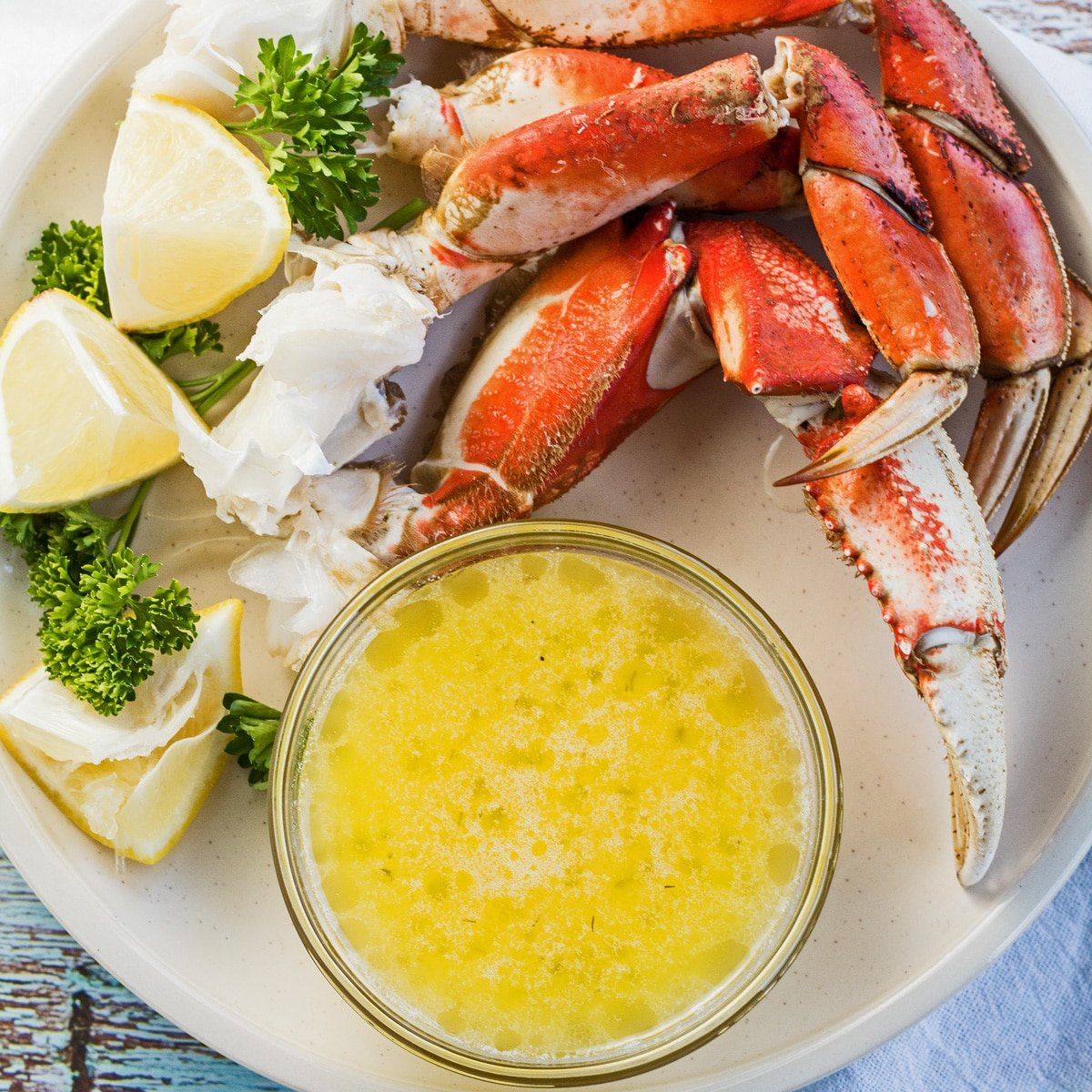 Drawn butter in clear bowl served on white plate with crab legs and lemon wedges.