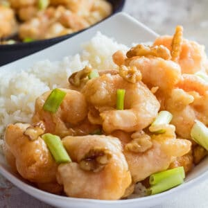 large square image of the panda express honey walnut shrimp served in a white bowl with green onions as garnish