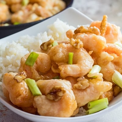 small square image of the panda express honey walnut shrimp served in a white bowl with green onions as garnish