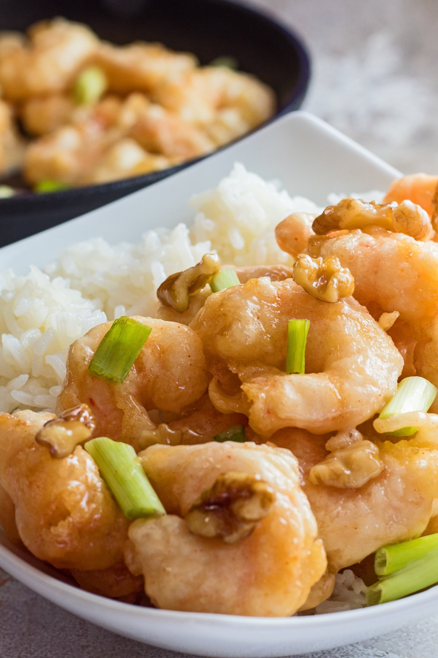 large vertical close up image of the panda express honey walnut shrimp served in a white bowl with green onions as garnish