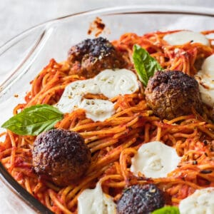 large square closeup image of baked spaghetti and meatballs in a clear casserole dish baked with fresh baby mozzarella and garnished with genovese basil leaves