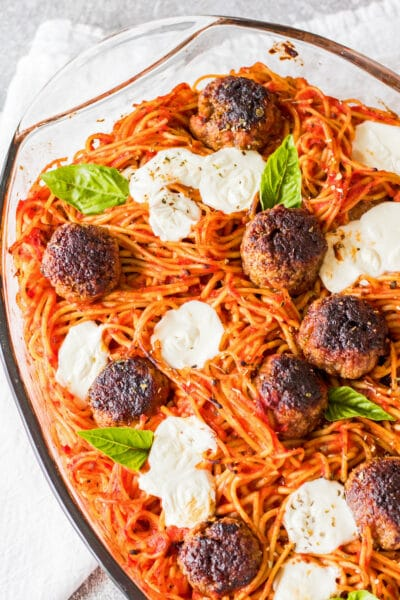 overhead vertical image of baked spaghetti and meatballs in a clear casserole dish baked with fresh baby mozzarella and garnished with genovese basil leaves on a light grey background