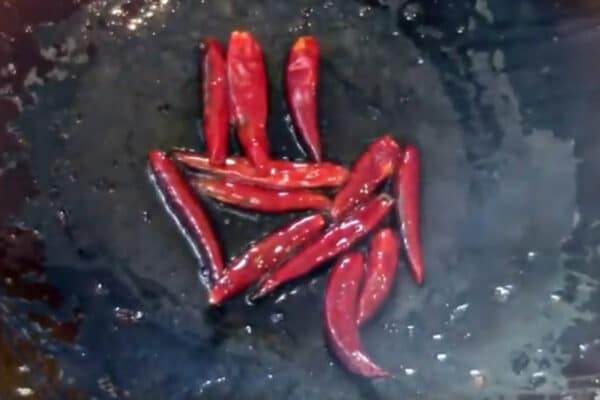 browning the whole dried chili peppers in the wok oil after stir frying the vegetables