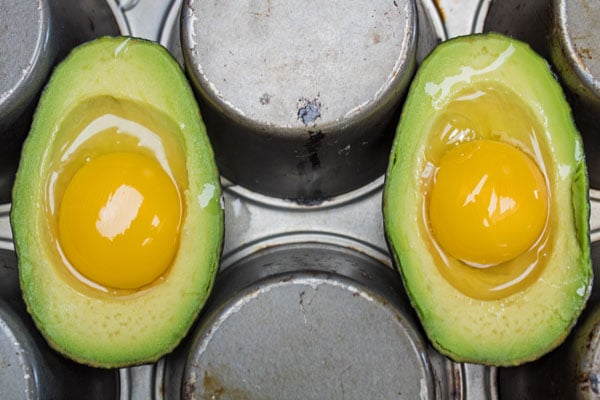 Preparing your baked avocados by holding them neatly in place in the back side of a muffin tin.