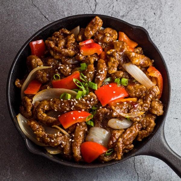 stort firkantet overheadbillede af panda express beijing oksekød serveret med wok stegte sprøde bidder af oksekød rød peber og løg i Beijing sauce