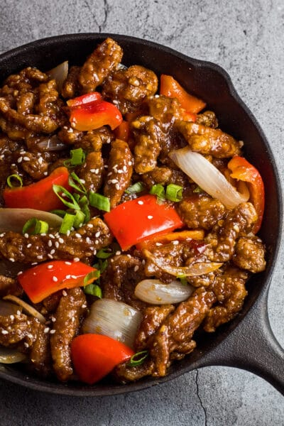 tall overhead photo of the beijing beef in the pan garnished with green onion and sesame seeds