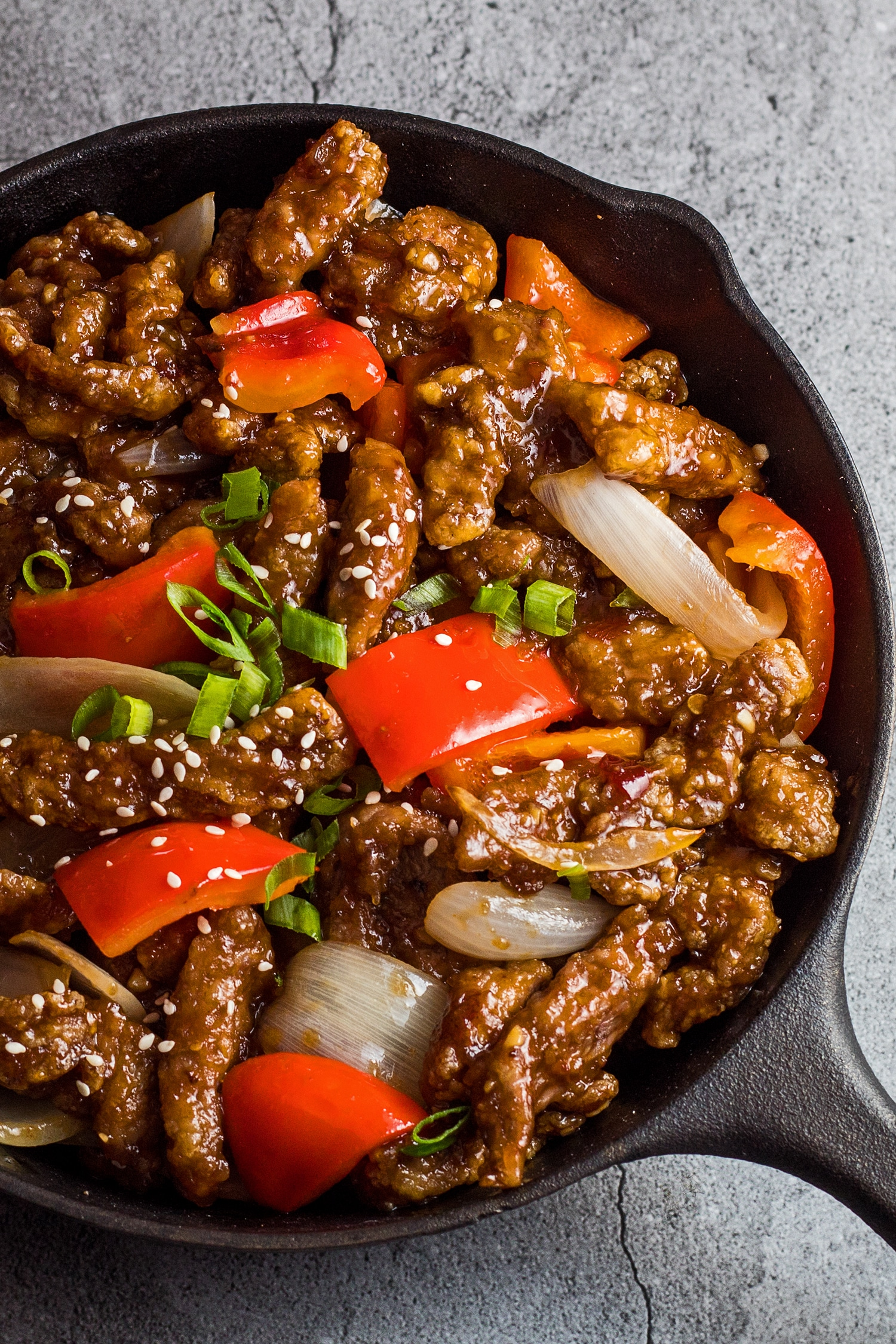 Tall overhead photo of the beijing beef in the pan garnished with green onion and sesame seeds.