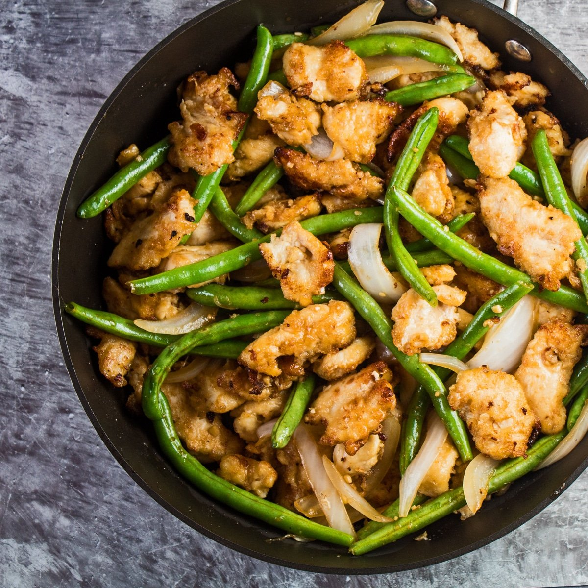 Large square overhead of the finished stir fried panda express string bean chicken before serving.