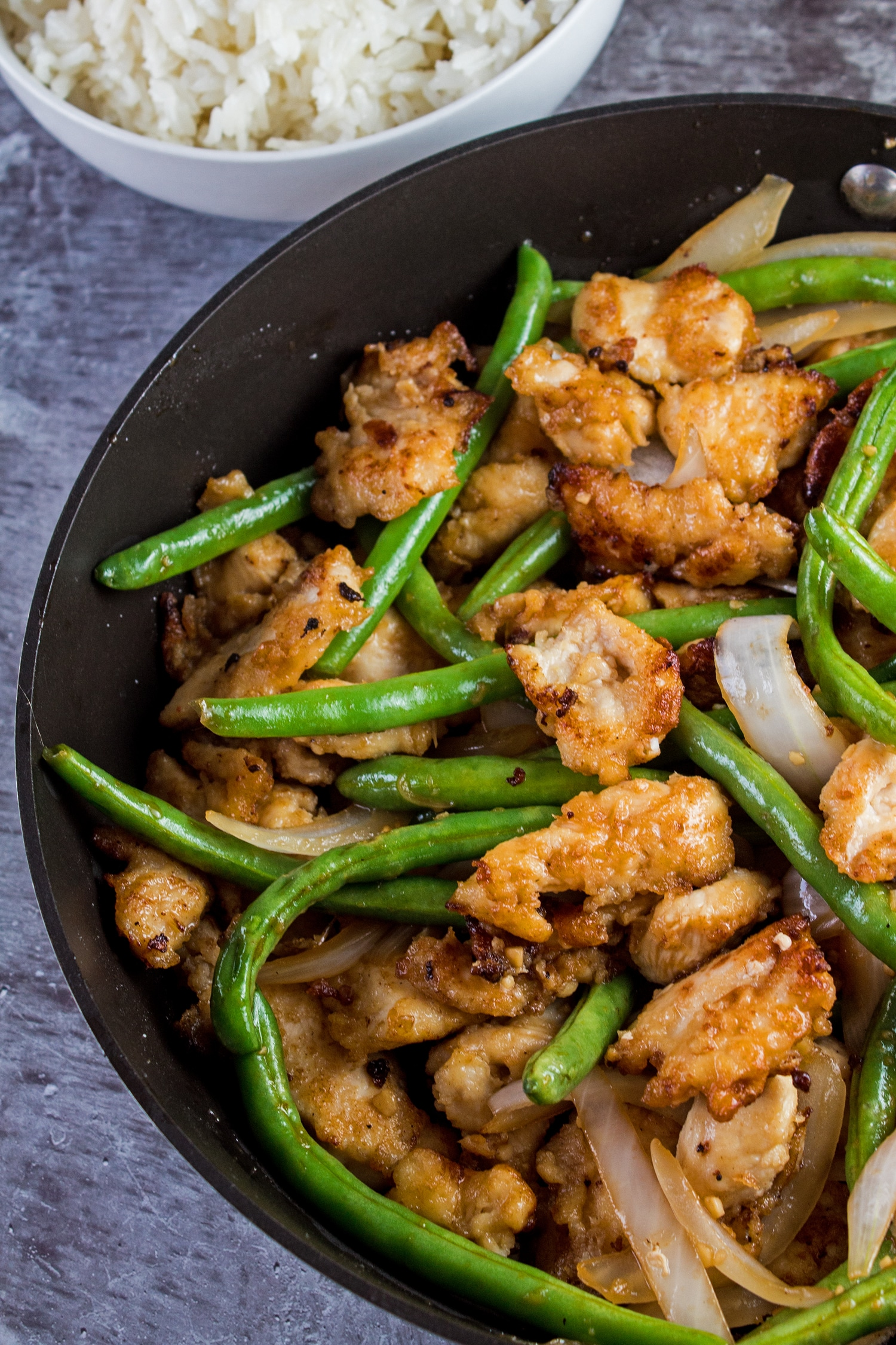 Tall vertical overhead image of the panda express string bean chicken with green beans, chunks of white onion and chicken breast pieces in a frying pan on grey background.