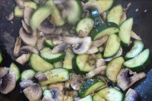 zucchini and mushrooms being stir fried with garlic and ginger added