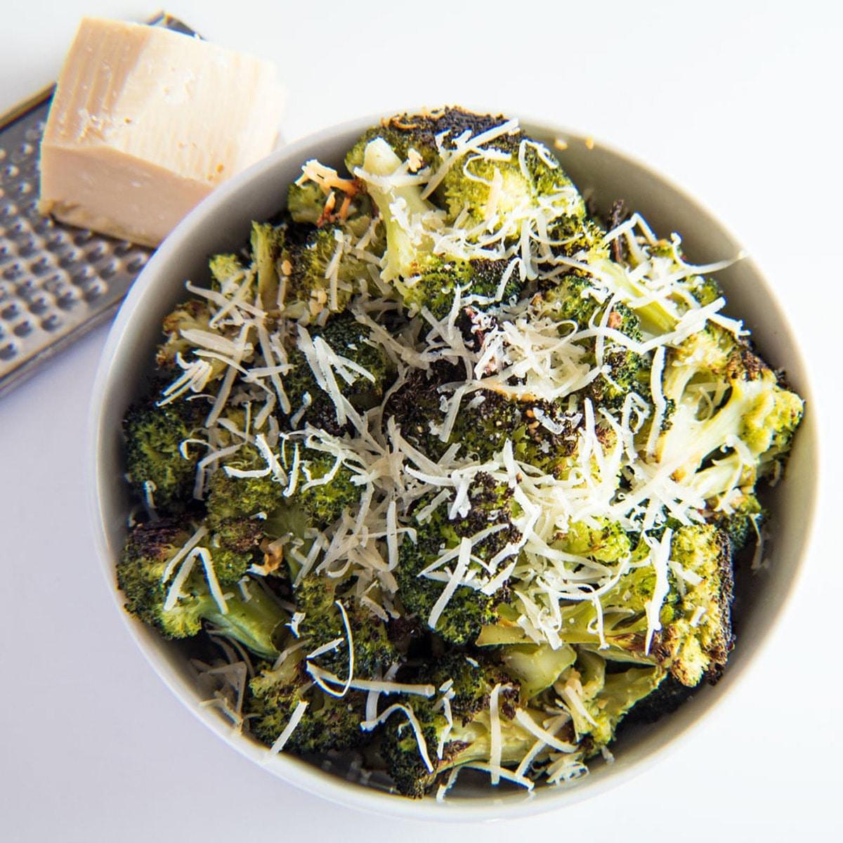 Rostad broccoli i en vit skål med parmesan ovanpå.