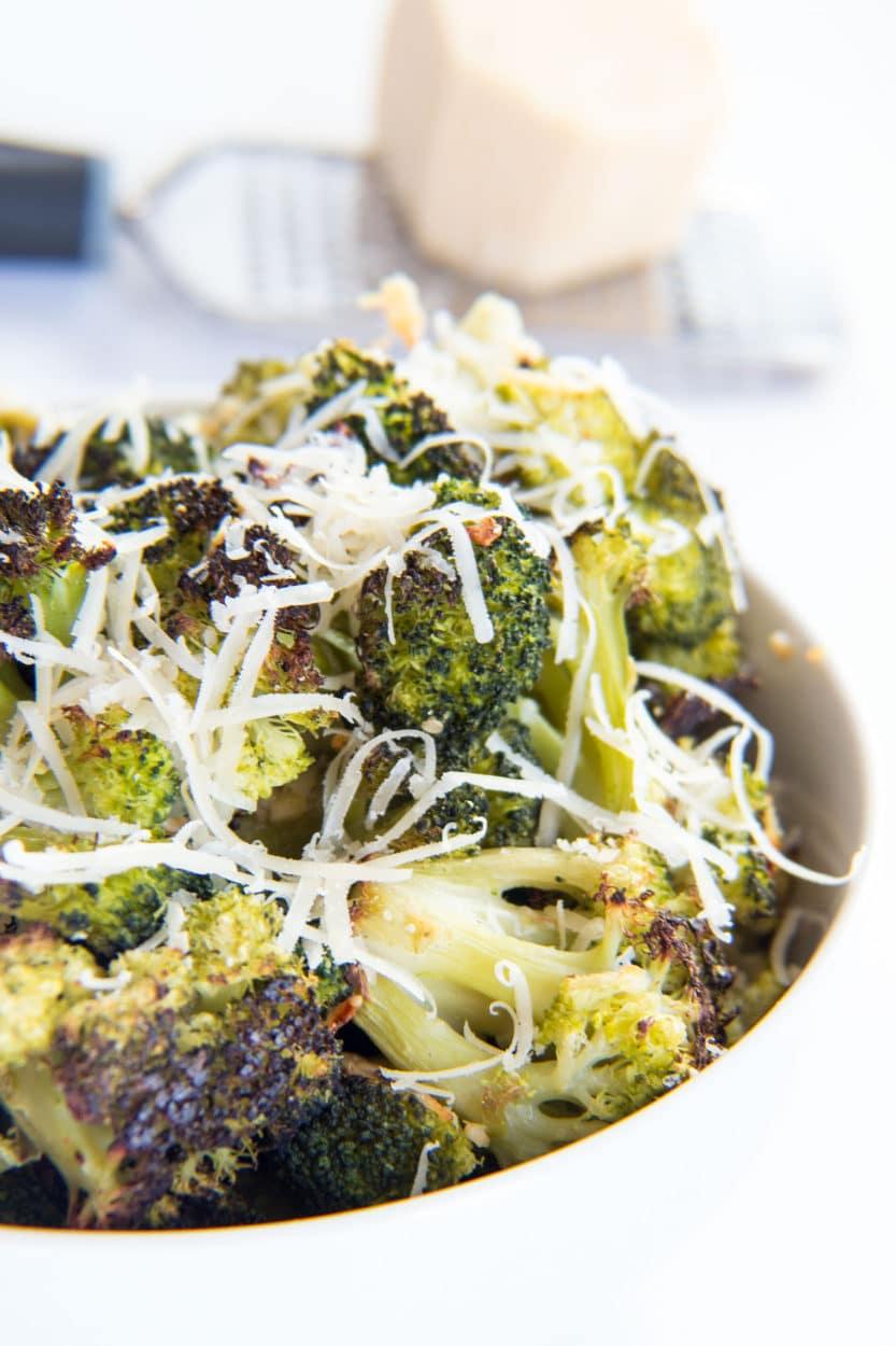 Lättrostad broccoli med vitlök och parmesan i en vit skål.