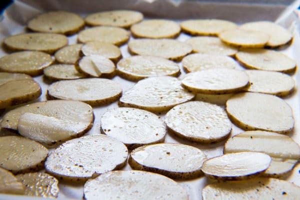 شرائح بطاطس مغموسة بزيت الزيتون ومتبلة للخبز قبل تحضير الناتشوز الأيرلندي.