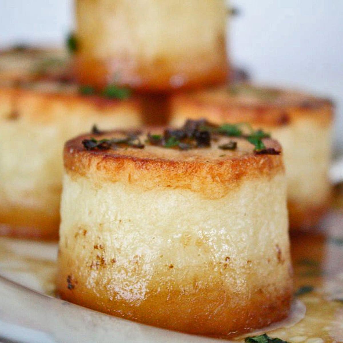 Fondantpotatis serveras på vit bricka med pannjuicer.