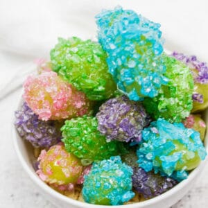 Sensational crack grapes (candied grapes) are a fun project to make with the kids, clear coated in candy syrup and dipped in crushed Jolly Rancher candies!