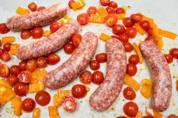 Se preparan salchichas italianas para hornear, con tomates cherry y pimientos.