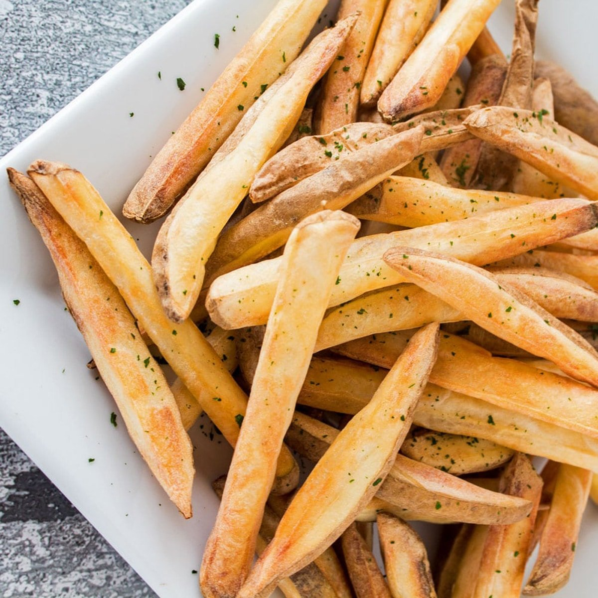 Air fried french fries on a white plate.
