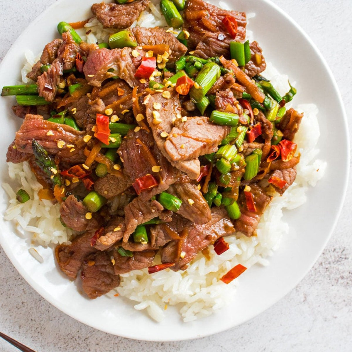 Hunan beef over a bed of white rice, on a white plate.
