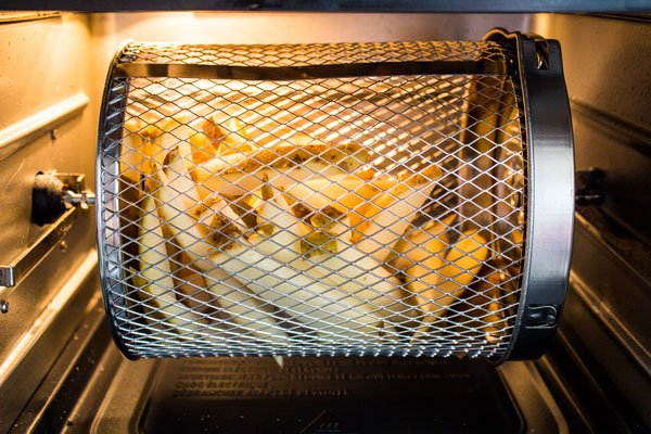 Freshly cut fries in the air fryer rotisserie basket of an Instant Pot Vortex Plus air fryer.