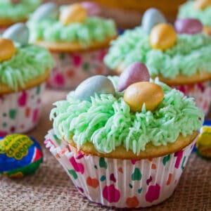 ¡Los deliciosos cupcakes de canasta de Pascua están cubiertos con glaseado de crema de mantequilla verde 'hierba' y cubiertos con mini huevos de chocolate con leche Cadbury!