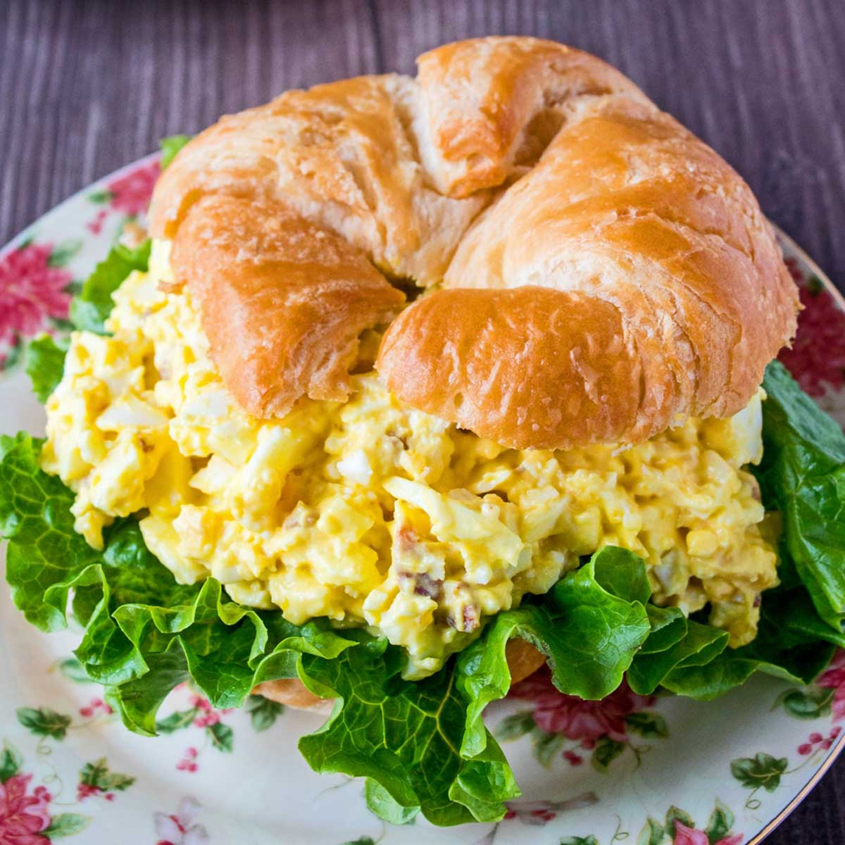 Egg salad sandwich on a floral plate.