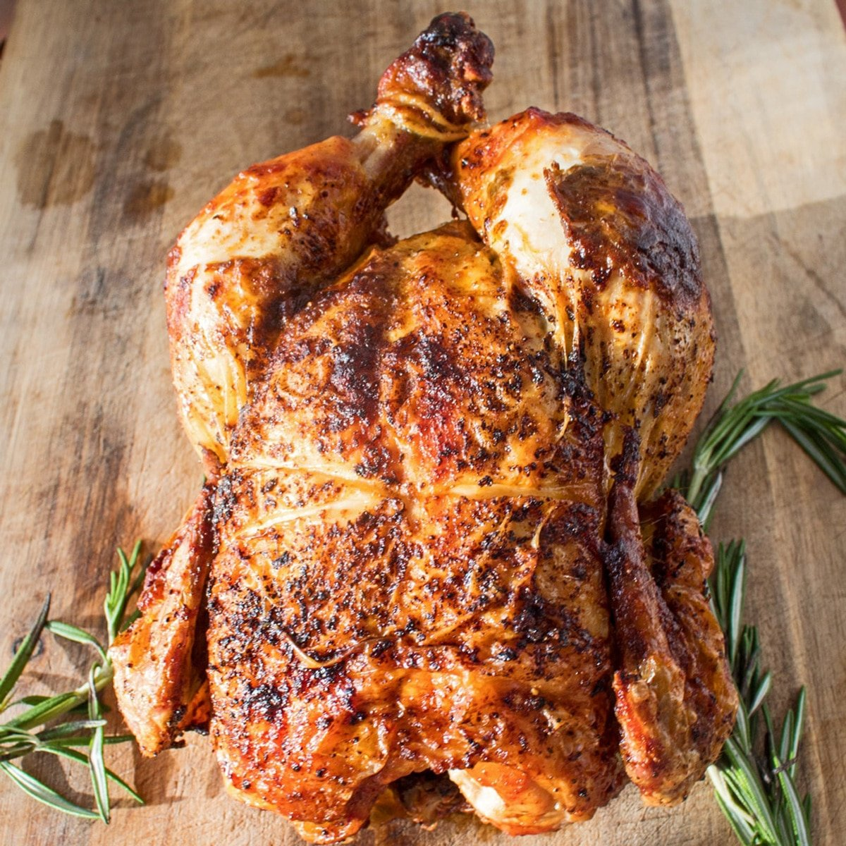 Rotisserie chicken on a cutting board with fresh rosemary.