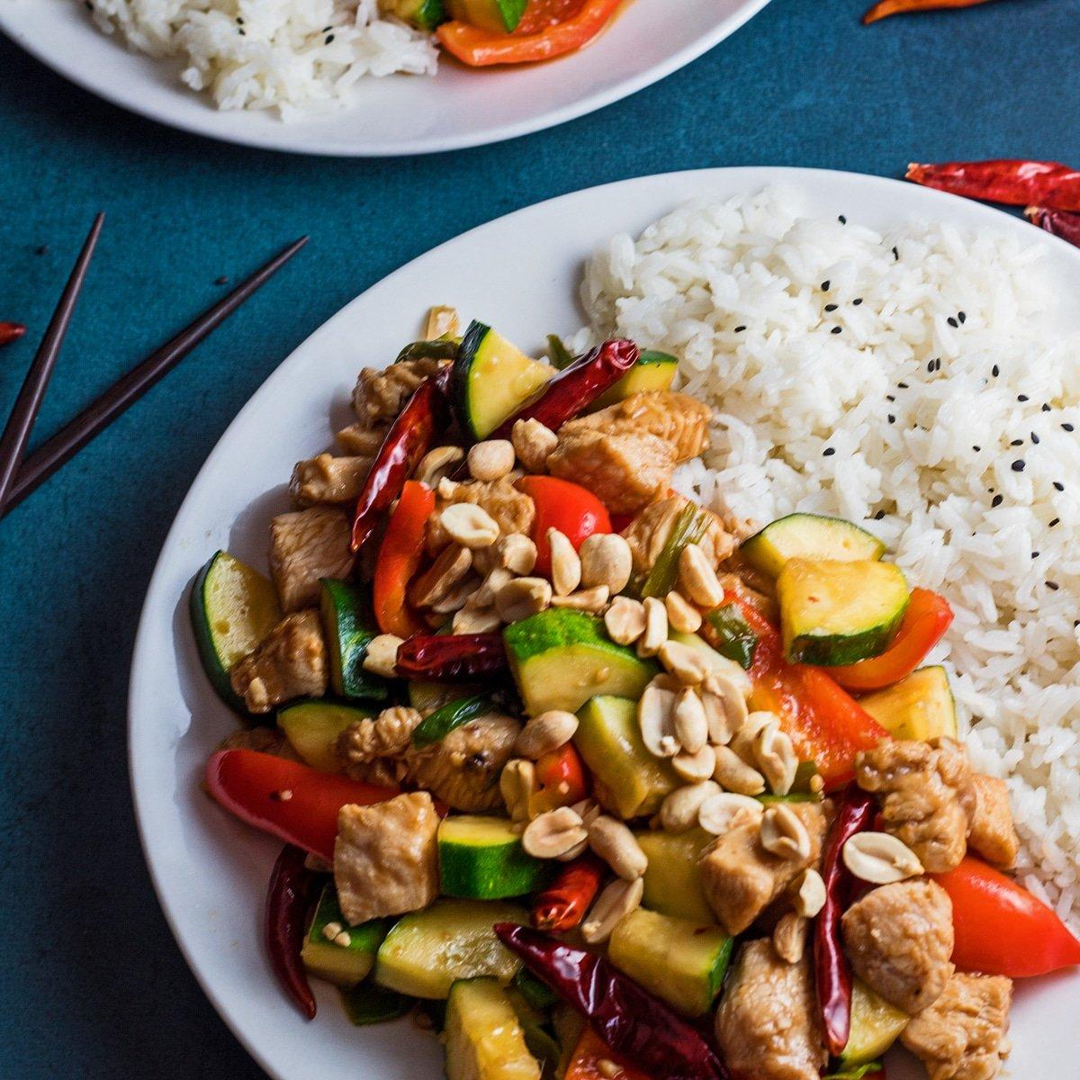 Imagen cuadrada grande de pollo Panda Express Kung Pao servido en un plato blanco con arroz sobre un fondo azul.