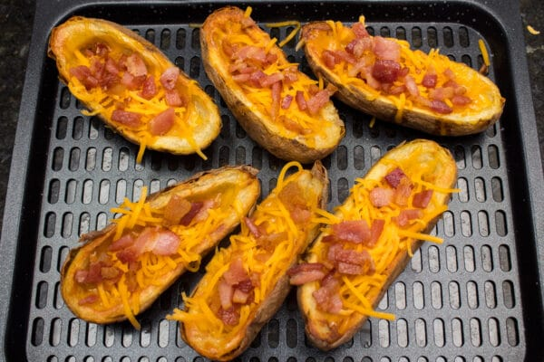 air fryer potato skins after being cooked for 10 minutes and with grated cheddar cheese and crumbled bacon added