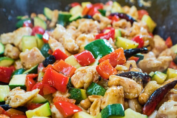 assembled kung pao chicken being wok fried, including bell peppers, zuchhini, chicken chunks, dried peppers and peanuts